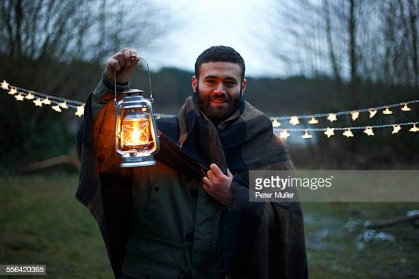 Young male camper holding up lantern whilst wrapped in blanket in woods