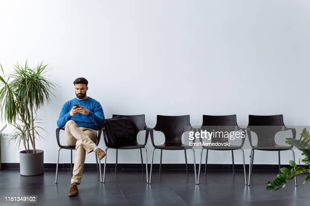 young male candidate using mobile phone while waiting for job interview - só um homem imagens e fotografias de stock