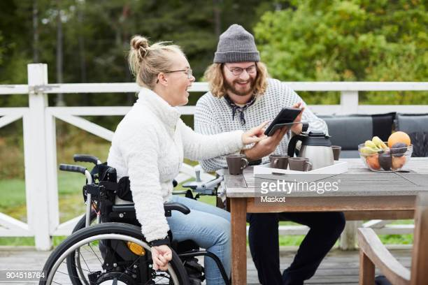young male caretaker and disabled woman using digital tablet in yard - autism spectrum disorder stock photos and pictures