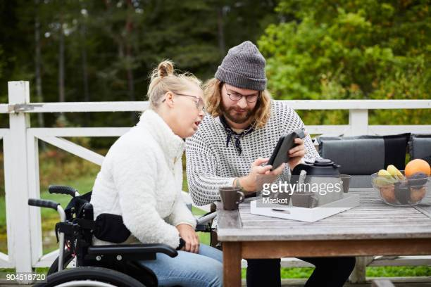 Young male caretaker using digital tablet with disabled woman in yard