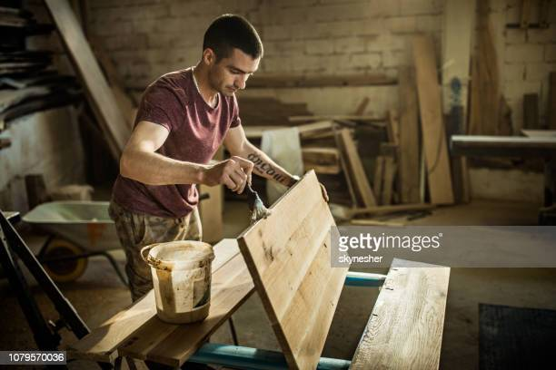 Young male carpenter applying varnish to piece of wood in a workshop.