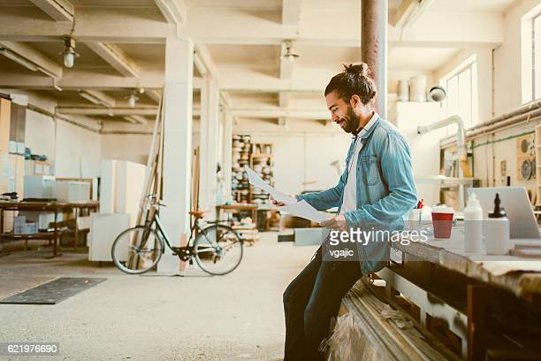 Young Male Carpenter Examining Blueprints In His Workshop