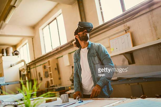 Young Male Carpenter Using VR Glasses In His Workshop