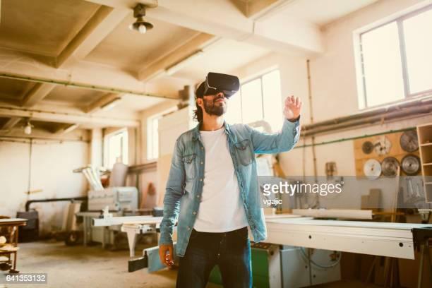 Junge männliche Zimmermann mit VR-Brille In seiner Werkstatt