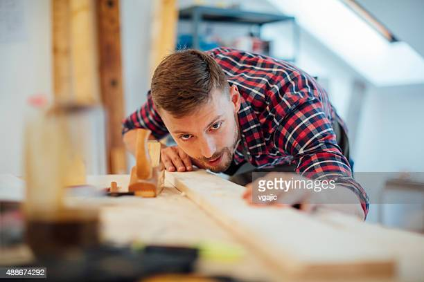 Young Male carpenter working on a project in his workshop.