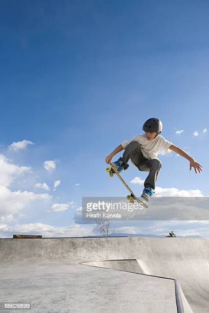 A young male catches some air in a skate park.