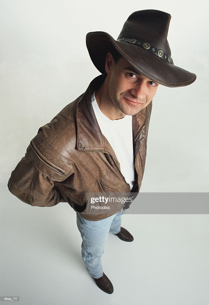 young male caucasian adult wearing a cowboy hat with a leather jacket stands looking up at the camera with a slight grin : Foto de stock
