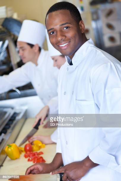 Young male chef chops vegetables in restaurant kitchen
