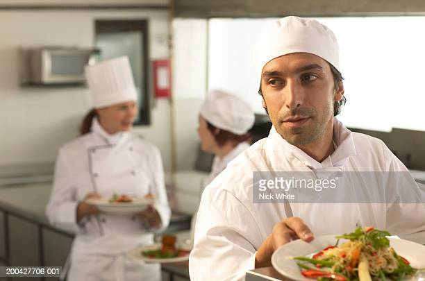 Young male chef placing dish on counter, looking away, close-up