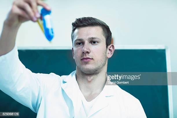 young male chemistry teacher closely observing the solutions in classroom, freiburg im breisgau, baden-w��rttemberg, germany - sigrid gombert stock pictures, royalty-free photos & images
