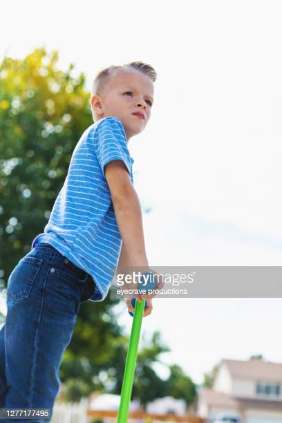 young male child looking into the distance while standing on a scooter - eyecrave  stock pictures, royalty-free photos & images