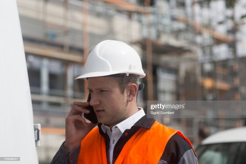 Young male civil engineer making smartphone call on construction site : Stock-Foto