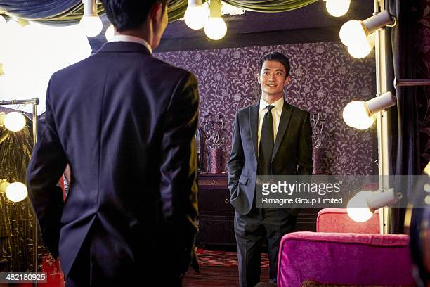 young male client trying on new suit in traditional tailors shop - custom tailored suit stock pictures, royalty-free photos & images