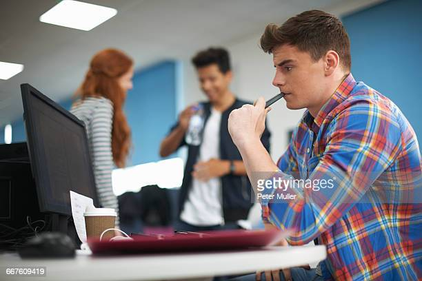 Young male college student at computer desk looking at computer