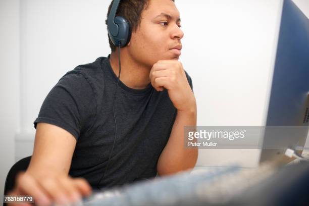 young male college student at mixing desk in tv studio - post-production stock pictures, royalty-free photos & images