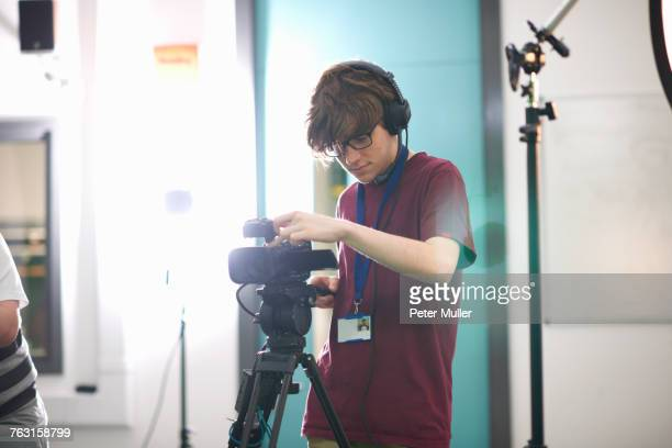 young male college student filming in tv studio - cinematographer stock pictures, royalty-free photos & images