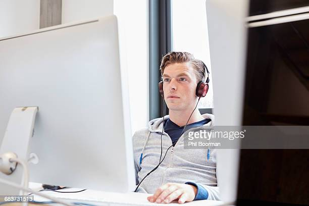 young male computer aided designer working on computer in design studio - hoodie headphones stock pictures, royalty-free photos & images