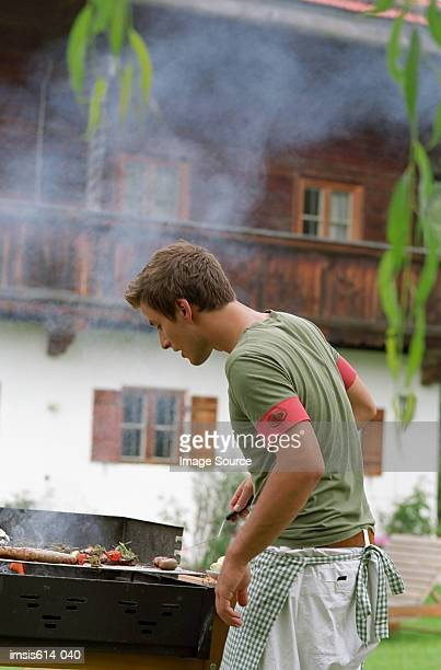 Young male cooks on barbeque