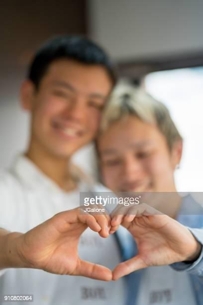 自分の手でハートの形を作る若い男性カップル