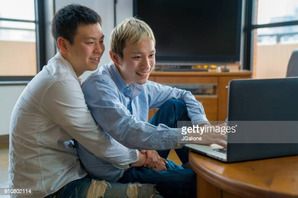 Young male couple using a laptop together at home
