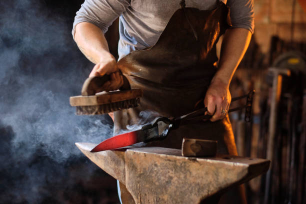 Young male craftsperson preparing metal knife on anvil at workshop