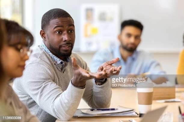 profesional creativo masculino joven pregunta durante la reunión - encogerse de hombros fotografías e imágenes de stock