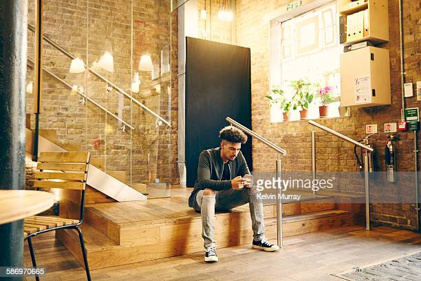 a young male creative professional uses smartphone - casual clothing stock pictures, royalty-free photos & images