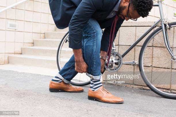 young male cyclist rolling down jeans on railway station platform - giacca da abito foto e immagini stock