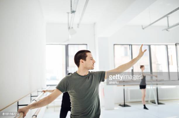 Young male dancer practicing ballet at barre