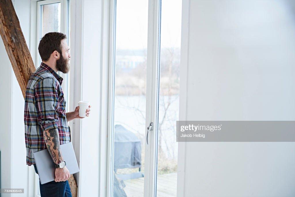 Young male designer looking through window in design studio : Stock-Foto