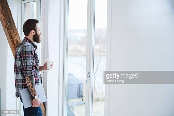 Young male designer looking through window in design studio