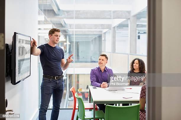 Young male designer making presentation in design studio