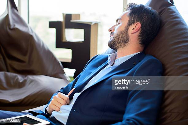 Young male designer sleeping on beanbag chairs in office