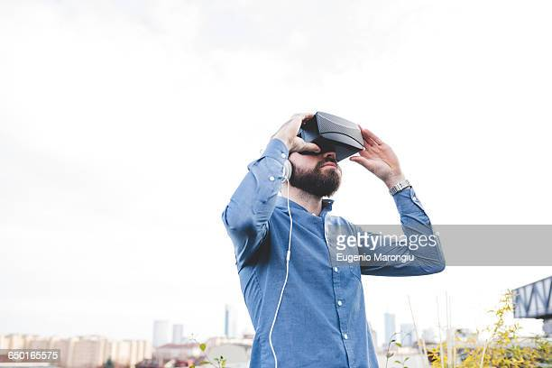 Young male designer testing virtual reality headset on office roof terrace