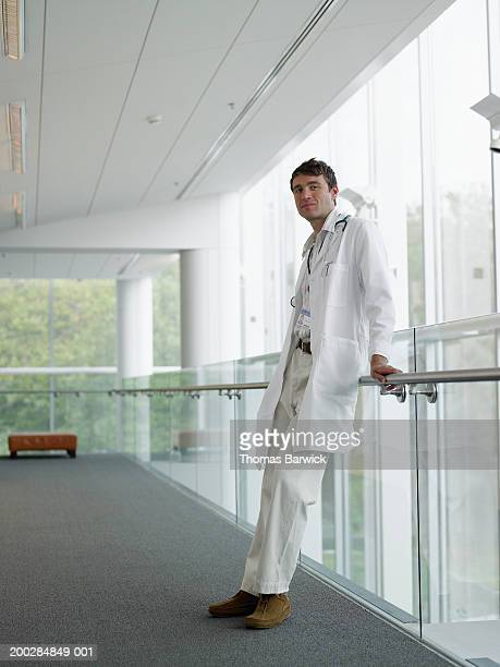Young male doctor leaning against railing in corridor, portrait