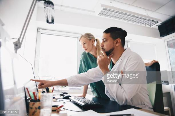 Young male doctor pointing at computer monitor to female nurse in office