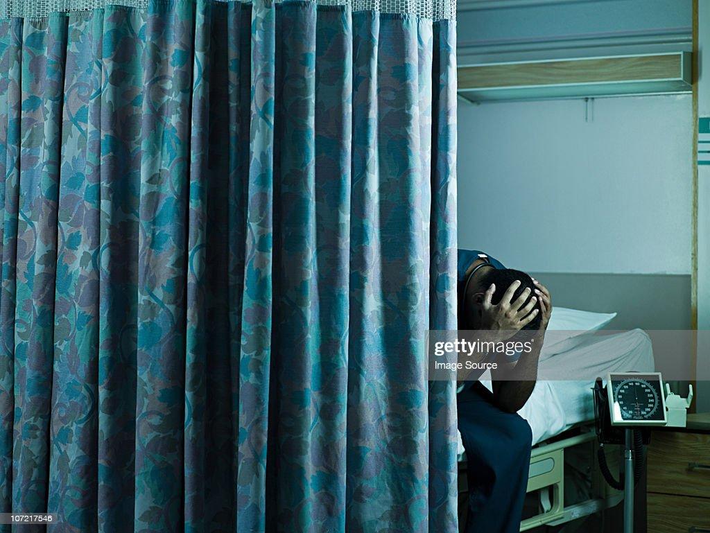 Jeune homme médecin assis sur le lit d'hôpital avec la tête : Photo