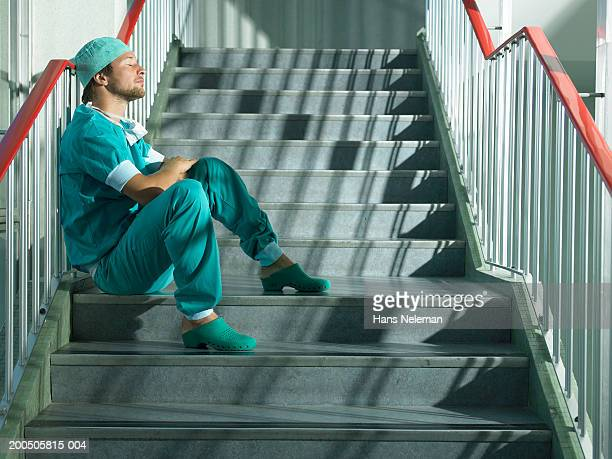 Young male doctor sitting on stairs, side view