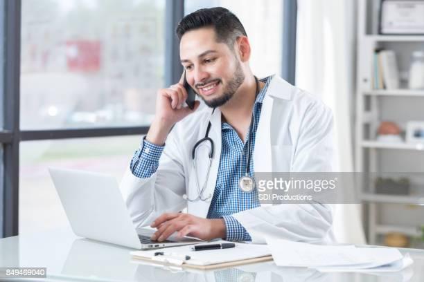 Jungen männlichen Arzt Gespräche am Telefon während der Nutzung der Computer während Forschung