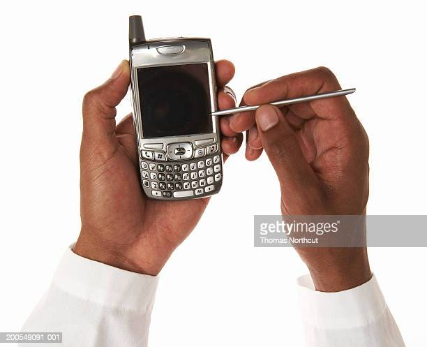 Young male doctor using palmtop, close-up of hands