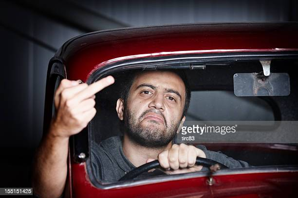 Young male driver giving the finger
