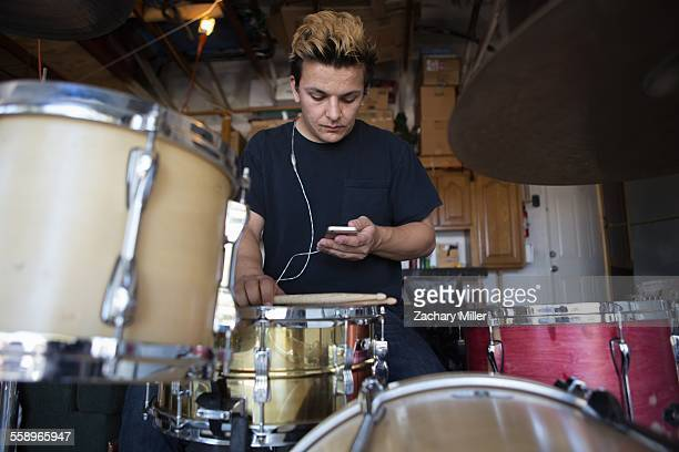 Young male drummer in basement reading smartphone texts