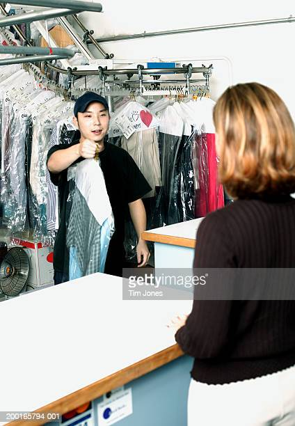 Young male dry cleaner retrieving garments for female customer