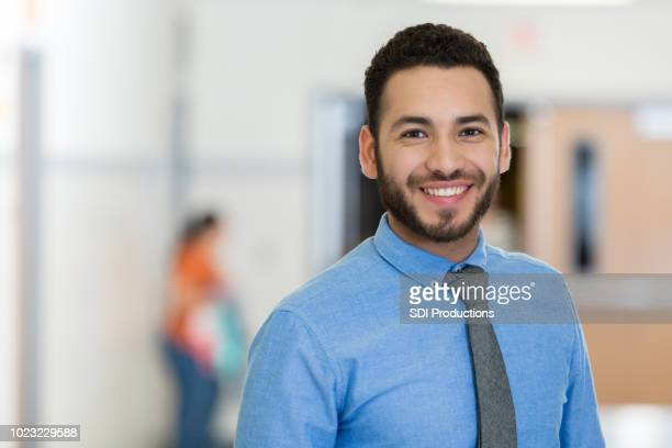 young male educator stands proudly in school building - males stock pictures, royalty-free photos & images