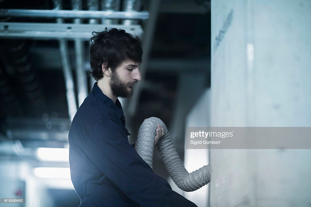 Young male engineer checking hose connection in an industrial plant, Freiburg im Breisgau, Baden-Württemberg, Germany : Stock-Foto