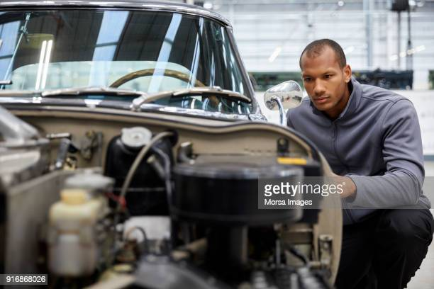 young male engineer examining car in industry - vintage auto repair stock pictures, royalty-free photos & images