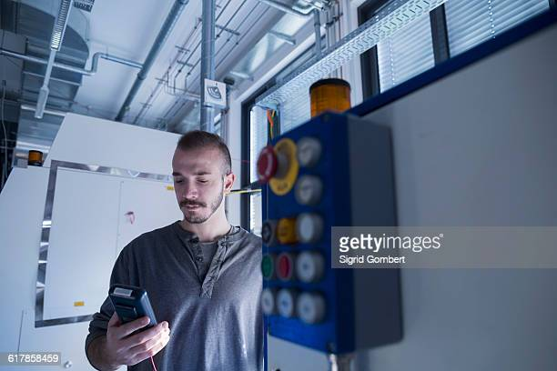 'Young male engineer examining control panel with multimeter in an industrial plant, Freiburg im Breisgau, Baden-Württemberg, Germany'