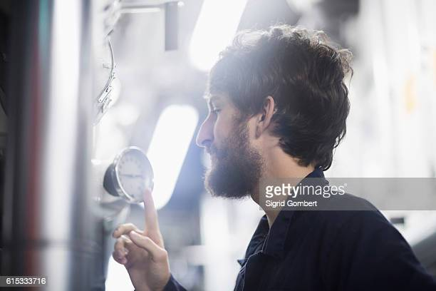 young male engineer examining gauge in an industrial plant, freiburg im breisgau, baden-württemberg, germany - sigrid gombert stock-fotos und bilder