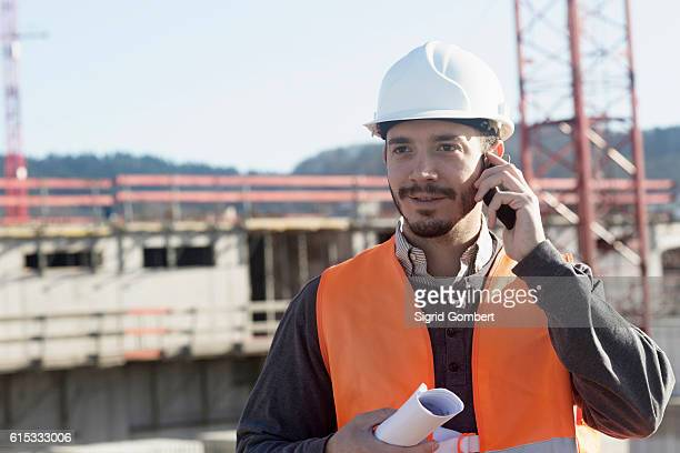 young male engineer holding blueprint and talking on a mobile phone at construction site, freiburg im breisgau, baden-württemberg, germany - sigrid gombert stock pictures, royalty-free photos & images