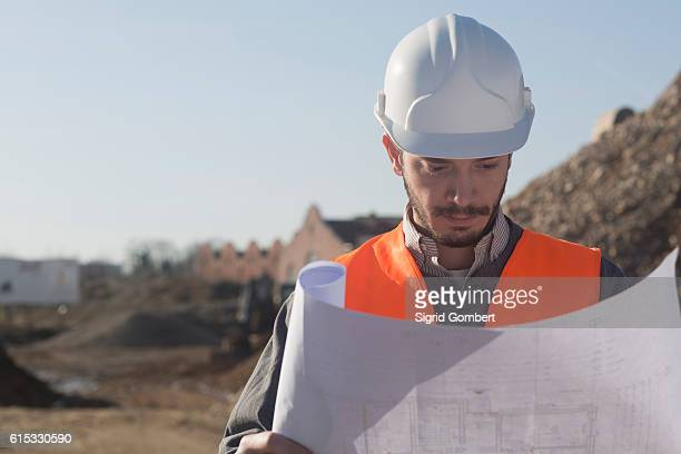 Young male engineer holding blueprint at construction site, Freiburg Im Breisgau, Baden-Württemberg, Germany